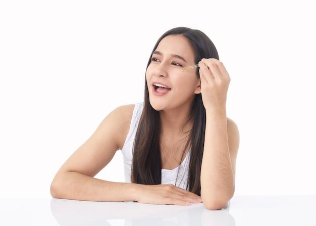Hautpflegekonzept. schönheitsporträt des lächelnden jungen asiatischen frauenmädchens, das pipette mit kosmetischem öl oder serum nahe dem sauberen gesicht hält. kosmetologie und spa