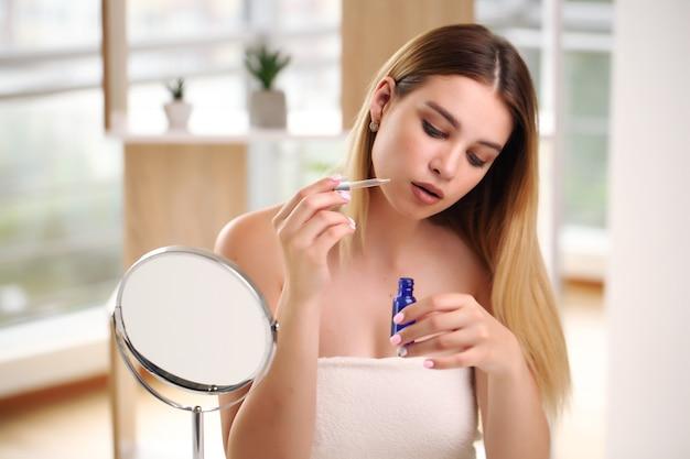 Hautpflegekonzept. schönheitsporträt des lächelnden mädchens der jungen frau, das pipette mit kosmetischem öl oder serum nahe sauberem gesicht hält. kosmetik und spa.