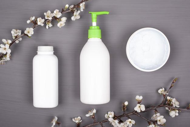 Hautpflegekosmetik, schönheit, spa. körperkosmetik in weißen flaschen auf grauem hintergrund mit zweigen der draufsicht der weißen kirschblumen