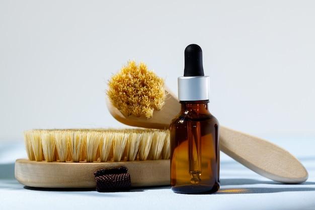 Hautpflegekosmetik und massagepinsel auf grauem hintergrund schließen