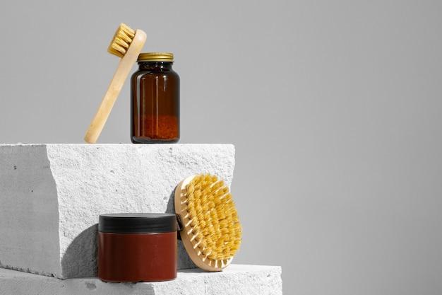 Hautpflegekosmetik und massagepinsel auf grauer nahaufnahme
