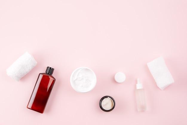 Hautpflegeprodukte auf pastellrosa oberfläche