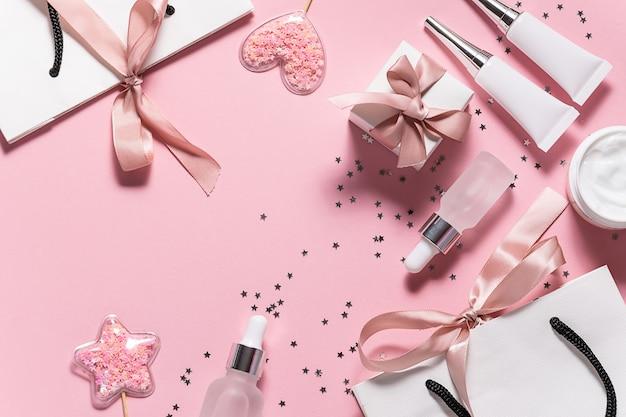 Hautpflegeprodukte in behältern ohne markenzeichen, geschenkboxen und taschen mit bändern, glänzende dekorationen