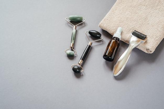 Hautpflegetools microneedling derma roller jade guasha massagerollen und serumflasche auf dem grauen b...
