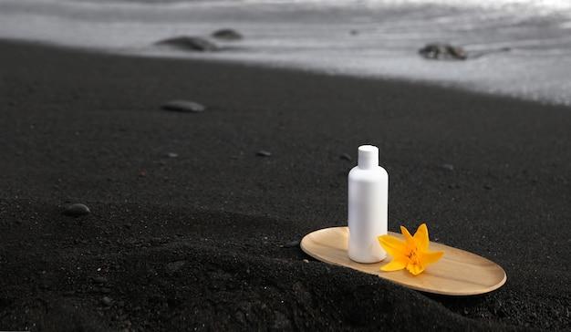 Hautpflegetubenprodukt auf schwarzem kanariensand.