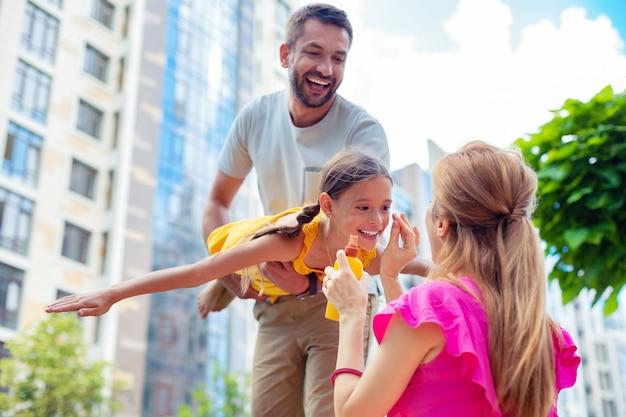 Hautschutz. nette fürsorgliche mutter, die sonnenschutzmittel zum schutz der haut ihrer töchter verwendet