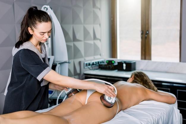 Hautstraffung, hüften und gesäß. hardware-kosmetologie für die körperformung. junge frau, die ultraschallkavitationskörperkonturierungsbehandlung, anti-cellulite-therapie im schönheitssalon erhält.