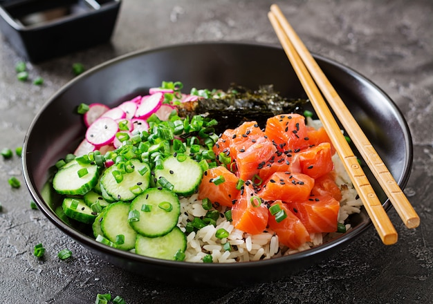 Hawaiian fish poke bowl mit reis, rettich, gurke, tomaten, sesam und algen.