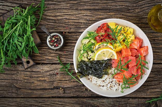 Hawaiian lachs fisch poke bowl mit reis, avocado, mango, tomate, sesam und algen.