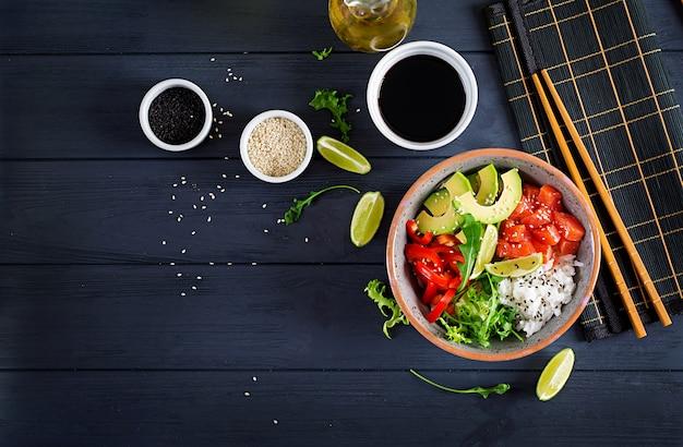 Hawaiian lachs fisch poke bowl mit reis, avocado, paprika, sesam und limette.