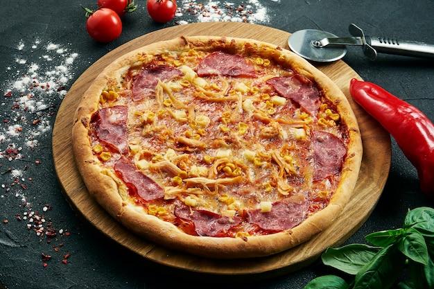 Hawaiianische pizza mit einer großen anzahl von belägen: schinken, ananas, mais und hühnchen. pizza in komposition mit zutaten auf einem schwarzen tisch