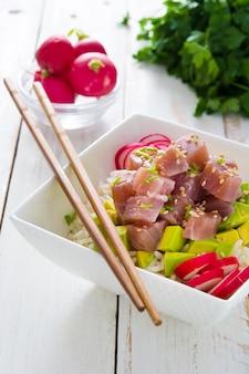Hawaiianische thunfisch-sackschale mit avocado, radieschen und sesam auf weißem holztisch