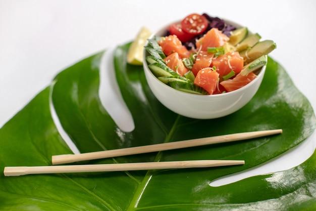 Hawaiische lachsstoßschüssel mit gurke, tomate, sesam, avocado.