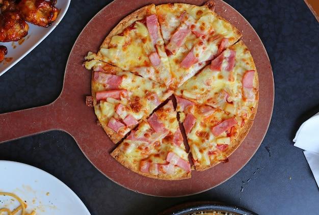 Hawaiische pizza auf einem hölzernen behälter
