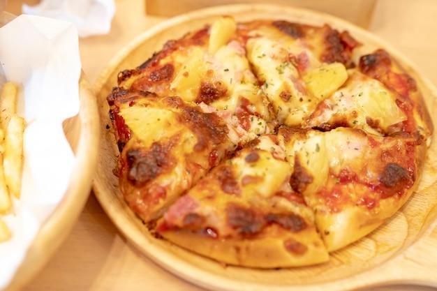 Hawaiische pizzeria und pommes-frites auf dem tisch im restaurant