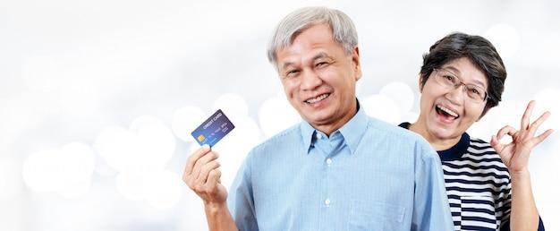 Header von glücklichen asiatischen netten älteren paaren, von rentnern oder von älteren eltern, die kreditkarte lächeln und zeigen