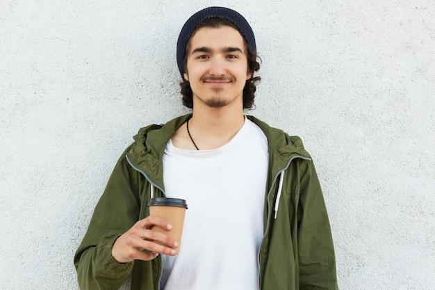Headshot des erfreuten hippie-kerls hält den mitnehmerkaffee, gekleidet im weißen t-shirt und in der grünen jacke, genießt freizeit, trägt schwarzen hut, modelle über weißem hintergrund, hat gelocktes haar. menschen und trinken