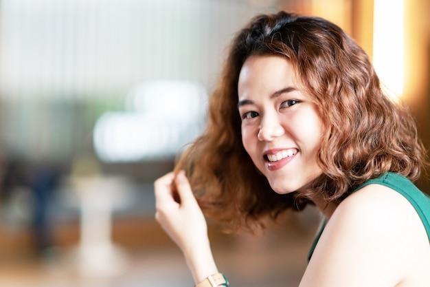 Headshot des jungen glücklichen attraktiven asiaten mit stilvollem weiblichem designer oder influencer des modischen gelockten brunettehaars, die kamera mit überzeugtem und positivem lächeln und betrachten. portrait des asiatischen netten mädchens.