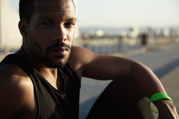 Headshot des nachdenklichen männlichen joggers der afroamerikaner, der sich nach intensivem training im freien entspannt