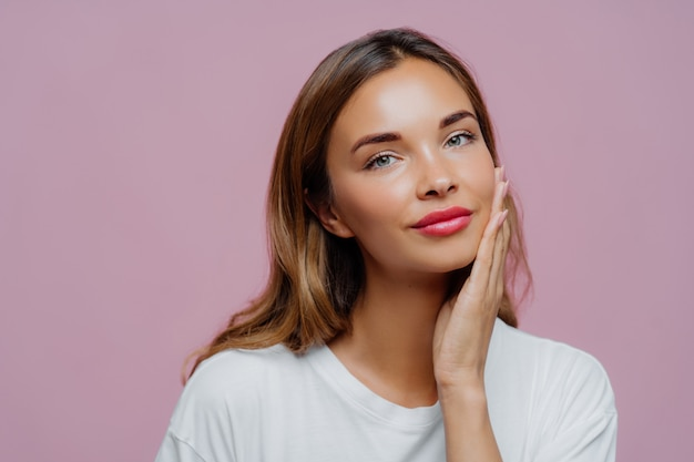 Headshot des reizenden weiblichen modells berührt leicht backe, genießt empfindliche gesichtshaut