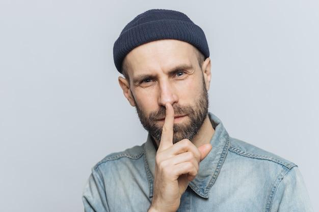 Headshot des stattlichen mannes mit starkem bart und dem schnurrbart, hat geheimen blick, demonstriert ruhezeichen