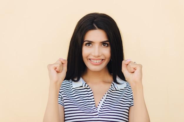 Headshot des weiblichen modells des glücklichen brunette ballt fäuste, hofft auf etwas gutes