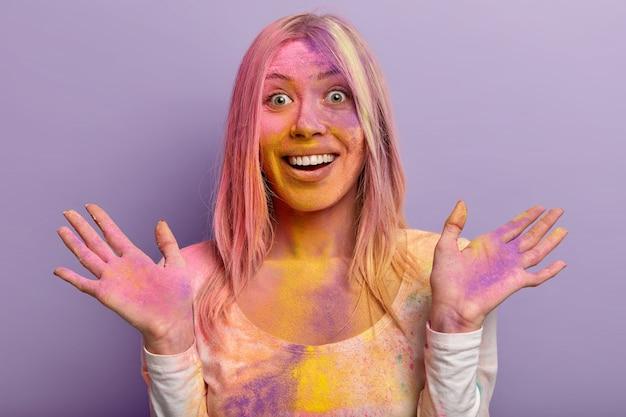 Headshot einer fröhlichen frau mit zahnigem lächeln, fröhlicher reaktion, ausgebreiteten händen, schmutzig mit mehrfarbigem trockenpulver, hat spaß am traditionellen holi-festival, isoliert gegen lila wand. leuchtende farben