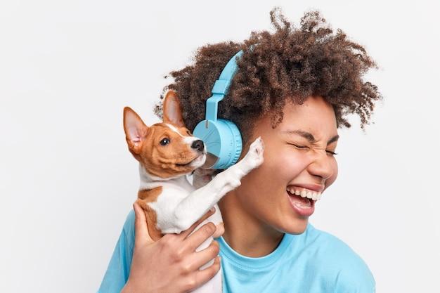 Headshot eines überglücklichen, lockigen teenager-mädchens hält einen kleinen schönen welpen mit zärtlichkeit, der gerne lieblingsmusik hört und zusammen mit dem haustier spazieren geht, das beste freunde ist. tiermenschen freude