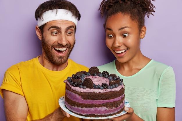 Headshot von glücklichen frauen und männern, die froh und überrascht sind, die erlaubnis des fitnesstrainers zu erhalten, leckeren kuchen zu essen