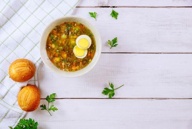 Healty sauerampfer suppe mit ei und knusprigen brötchen