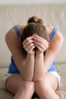 Heartbroken frau, die den ehering, zerbröckelnd hält