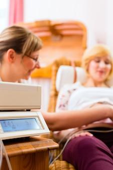 Hebamme, die mutter für schwangerschaftsuntersuchung sieht