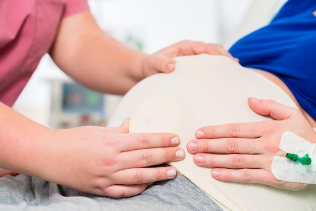 Hebammen- oder krankenschwestergefühlbabybauch der schwangeren frau