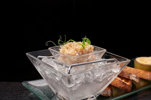 Hechtfischkaviar auf eis mit croutons und butter auf einer transparenten schale auf dunklem hintergrund