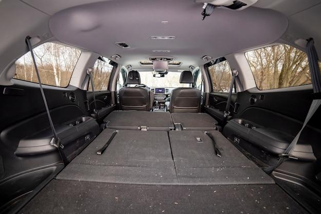 Heckansicht offener kofferraum mit umgeklappten beifahrersitzen. großer leerer flacher flor autokofferraum hautnah. riesiger suv kofferraum