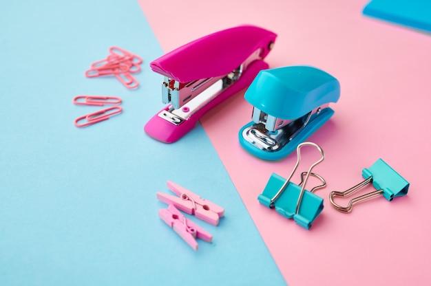 Hefter und büroklammern nahaufnahme, blauer und rosa hintergrund. büromaterial, schul- oder bildungszubehör, schreib- und zeichenwerkzeuge