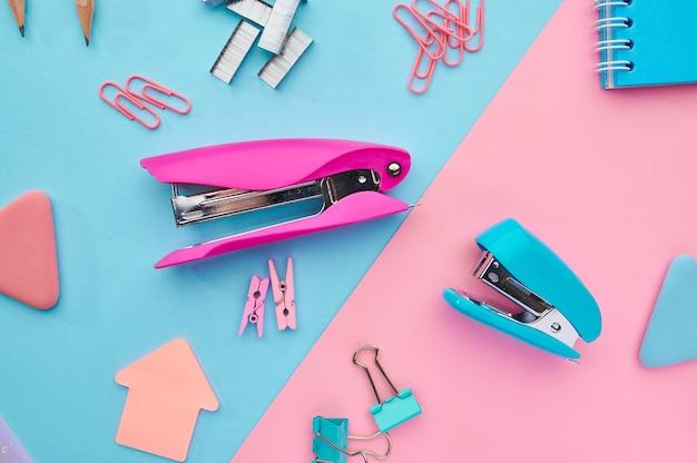 Hefter und büroklammern nahaufnahme, blauer und rosa hintergrund. büromaterial, schul- oder bildungszubehör