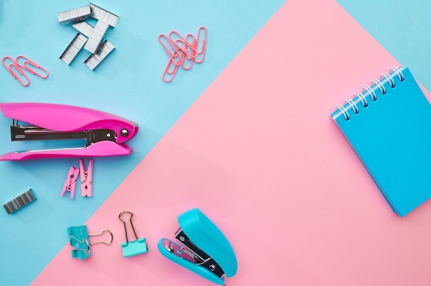 Hefter und büroklammern nahaufnahme, blauer und rosa hintergrund. büromaterial, schulzubehör