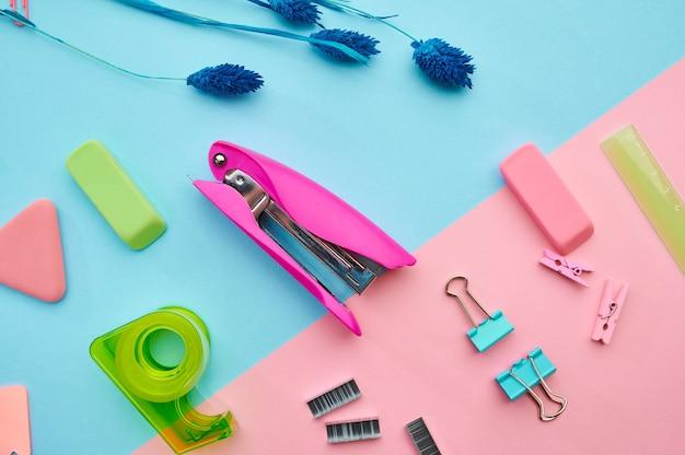 Hefter und clips nahaufnahme, blauer hintergrund. büromaterial, schul- oder bildungszubehör, schreib- und zeichenwerkzeuge