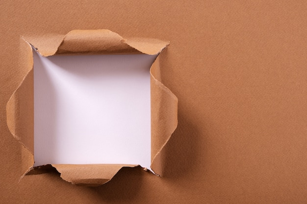 Heftiger hintergrundrahmen des quadratischen lochs des braunen papiers