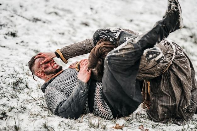 Heftiger kampf zweier junger krieger in rüstung auf dem boden im schnee ohne waffen