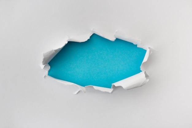 Heftiges loch in der weißen farbe und vom papier mit blauem hintergrund zerrissen. zerrissene papierbeschaffenheit mit kopienraumbereich für text