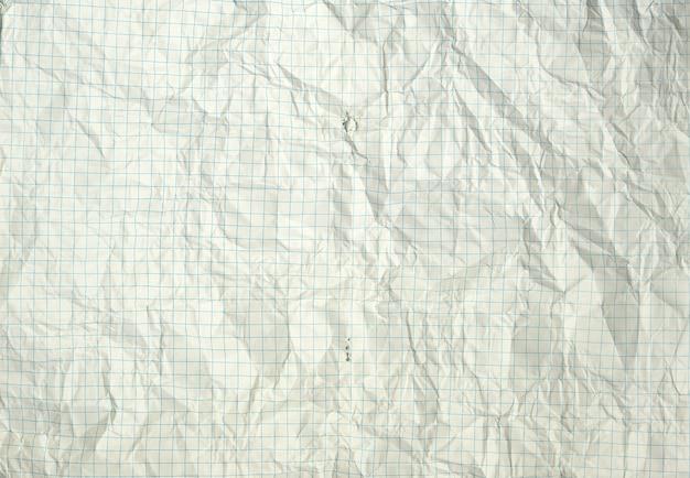 Heftiges und geknittertes weißes leeres quadratisches blatt von einem schulnotizbuchhintergrund