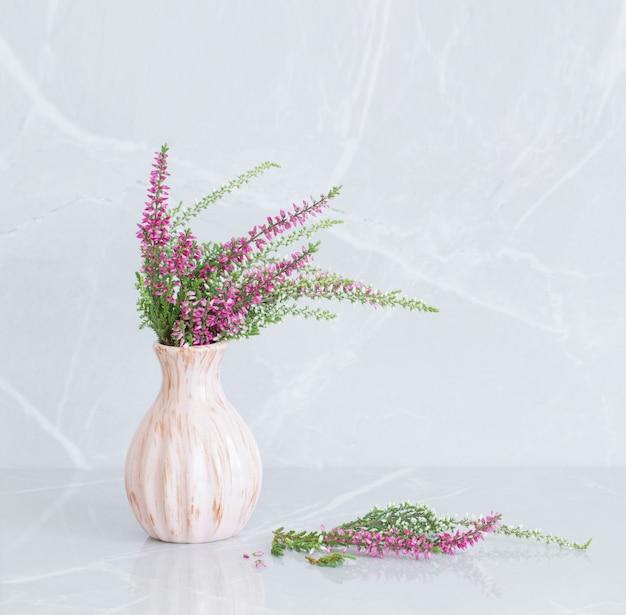 Heideblumenstrauß in vase auf grauem marmorhintergrund