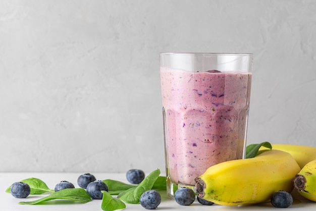 Heidelbeer-, bananen- und spinat-smoothie oder milchshake in einem glas mit frischen früchten und beeren