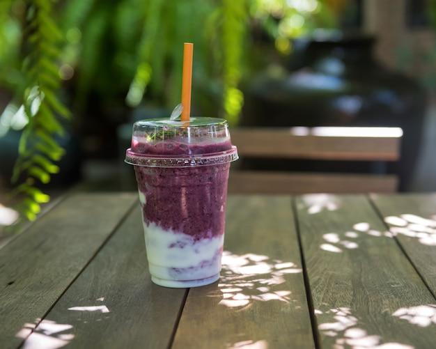 Heidelbeer-joghurt-smooties auf holztisch des café-gartencafés mit verwischtem laublicht bokeh