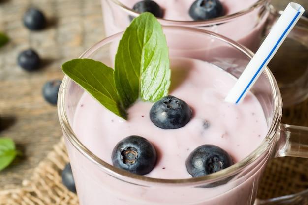 Heidelbeerjoghurt in den glasschalen mit frischen blaubeeren und minze auf einer hölzernen rustikalen tabelle