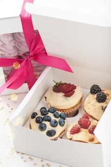 Heidelbeerköstliche kleine kuchen in einem papierkasten