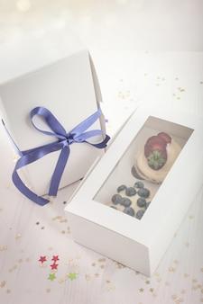 Heidelbeerköstlicher kleiner kuchen in einem papierkasten