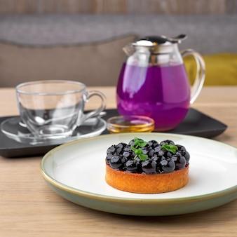 Heidelbeertorte und blauer tee erbsenblüte kräutertee. thailändischer blauer tee serviert mit honig und blaubeerkuchen auf holztisch